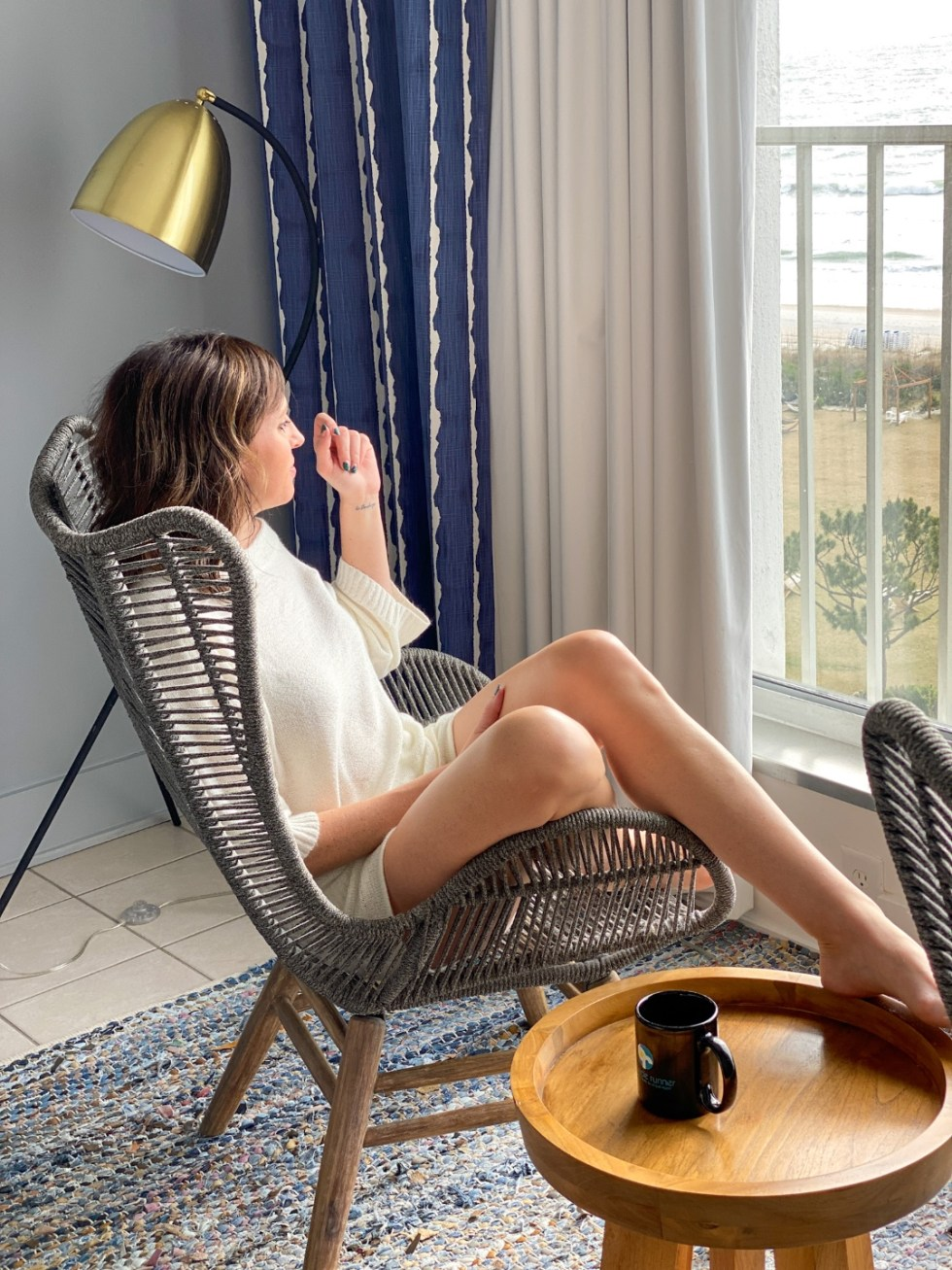 A Spring Weekend in Wilmington, NC: the Best Things to Do - I'm Fixin' To - @imfixintoblog |Weekend in Wilmington by popular NC travel blog, I'm Fixin' To: image of a woman sitting in a lounge chair and looking out a large window.