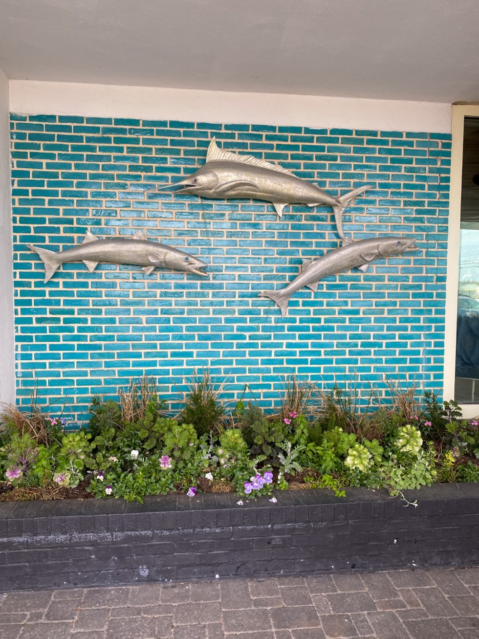 A Spring Weekend in Wilmington, NC: the Best Things to Do - I'm Fixin' To - @imfixintoblog |Weekend in Wilmington by popular NC travel blog, I'm Fixin' To: image of metal fish decor mounted onto a wall with blue subway tile.