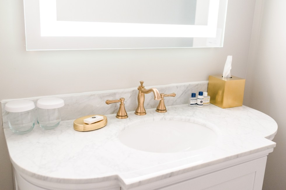 Places to Stay: The Colonial Inn in Hillsborough NC - I'm Fixin' To - @imfixintoblog |The Colonial Inn Hillsborough NC by popular NC travel blog, I'm Fixin' To: image of a bathroom vanity with a white marble counter top and gold faucet.