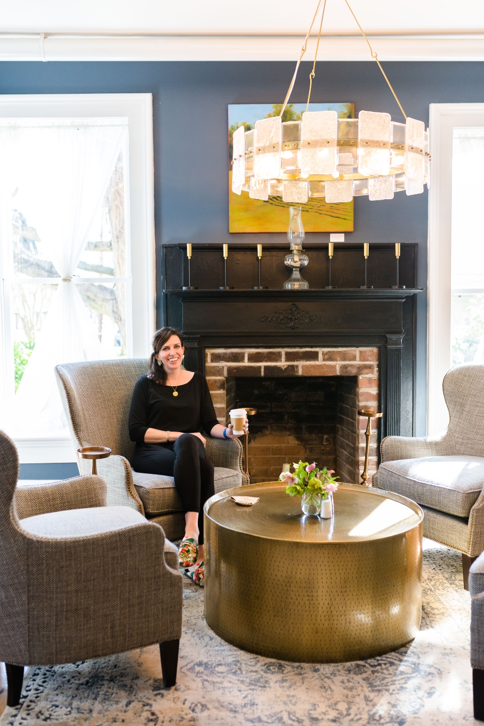 Places to Stay: The Colonial Inn in Hillsborough NC - I'm Fixin' To - @imfixintoblog |The Colonial Inn Hillsborough NC by popular NC travel blog, I'm Fixin' To: image of a sitting area with a blue wall, brick fireplace, round gold coffee table, and grey fabric wingback chairs.
