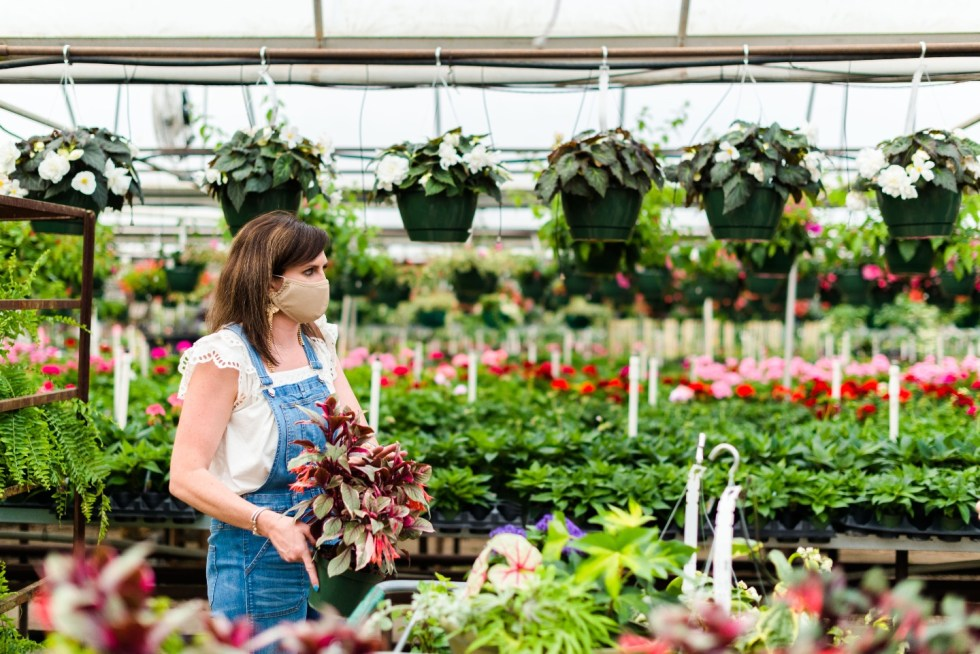 5 Spring Planting Tips with Fairview Garden Center - I'm Fixin' To - @imfixintoblog |Best Plants to Plant in Spring by popular NC lifestyle blog: image of a woman holding some plants at the Fairview Garden Center.