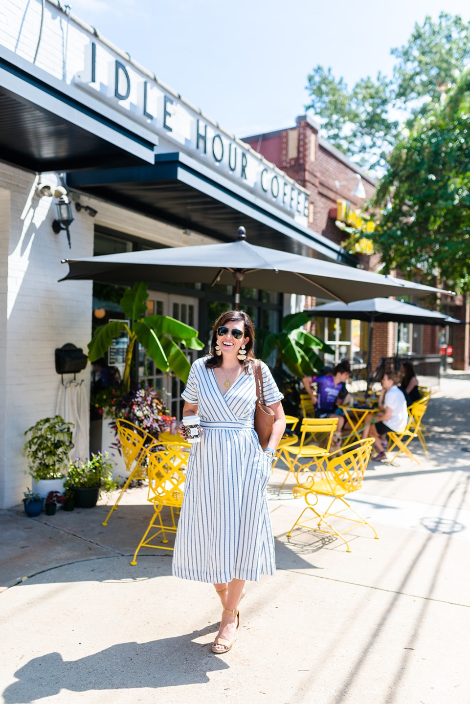 Social Media Free Sunday by popular NC lifestyle blog, I'm Fixin' To: image of a woman walking outside by some yellow tables and chairs and wearing a white and blue stripe dress.