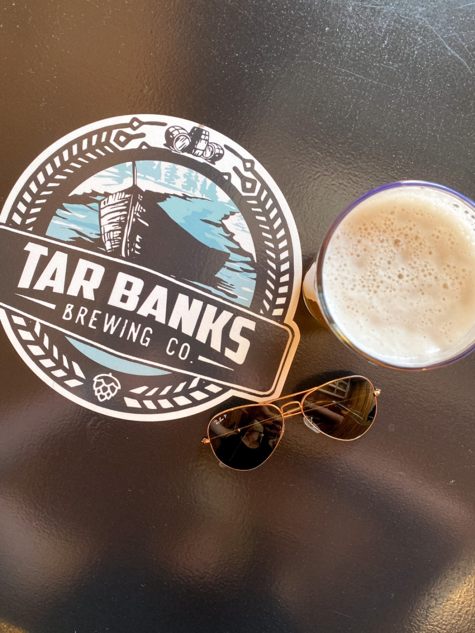 An Afternoon Trip to Franklin County, NC - I'm Fixin' To - @imfixintoblog | Franklin County NC by popular North Carolina travel blog, I'm Fixin' To: image of a Tar Banks Brewing Co coaster next to a glass of beer and aviator sunglasses.