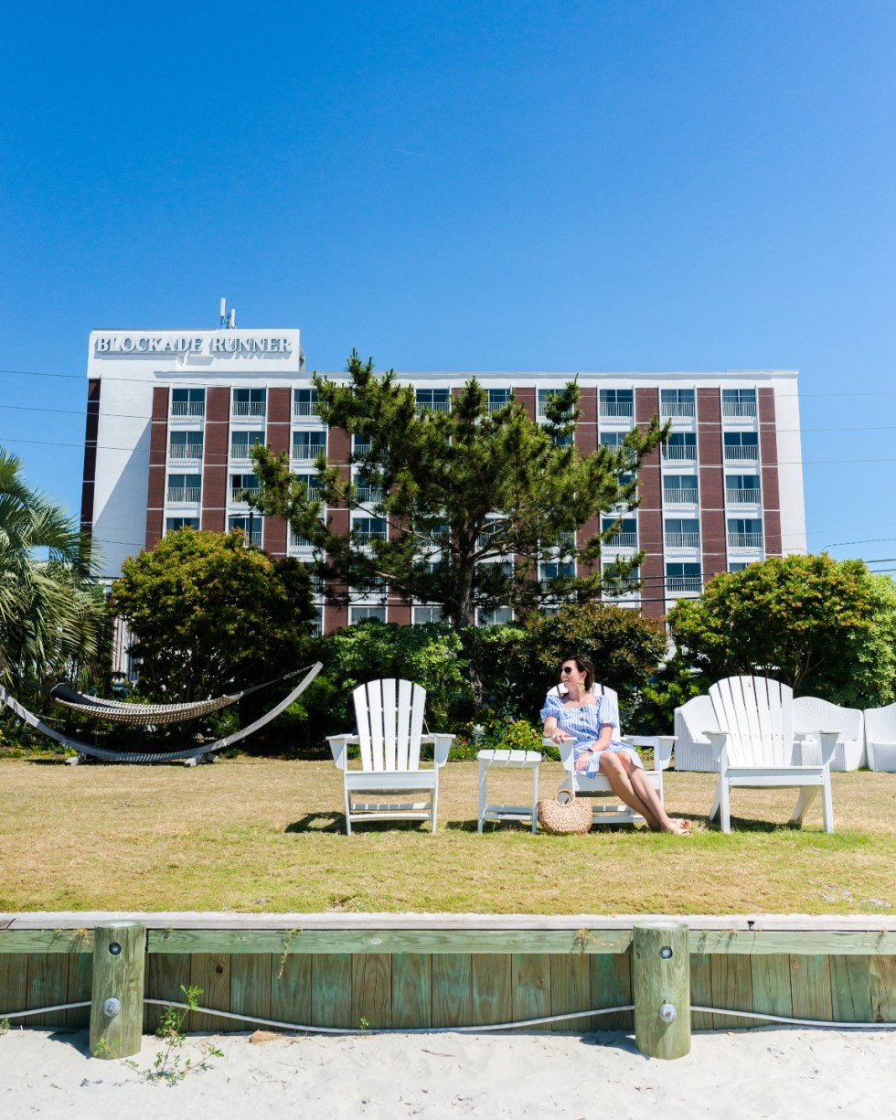 The Blockade Runner Hotel by popular NC travel blog, I'm Fixin To: image of a woman sitting in a wooden white lounge chair in front of the Blockade Runner hotel.