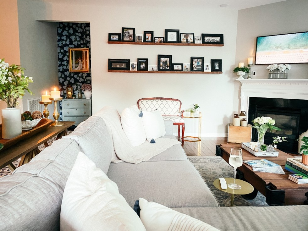 Room Reveal: Blue and Gray Living Room Ideas - I'm Fixin' To - @imfixintoblog | Blue and Grey Living Room Ideas by popular NC life and style blog, I'm Fixin' To: image of a living room decorated with a blue and white rug runner, light wood sofa table, house plants, floating wood shelves with black picture frames, white pillar candles, wooden picnic basket, blue and white floral wallpaper, and vintage blue and white armchair.