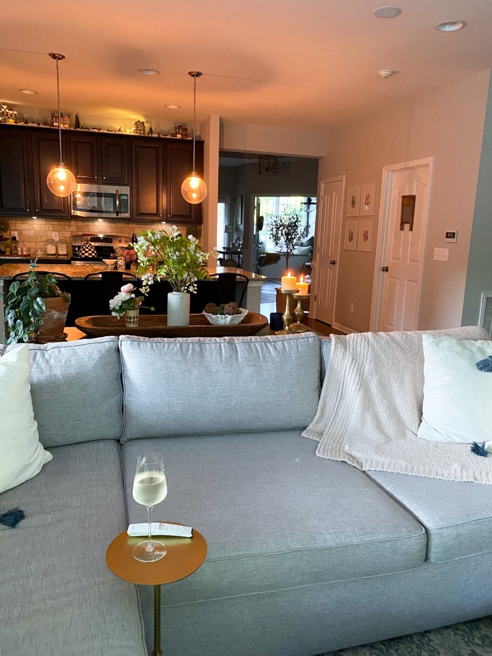 Room Reveal: Blue and Gray Living Room Ideas - I'm Fixin' To - @imfixintoblog | Blue and Grey Living Room Ideas by popular NC life and style blog, I'm Fixin' To: image of a living room decorated with a grey sectional couch white throw pillow, cream cable knit blanket, potted house plants, and blue and white area rug.