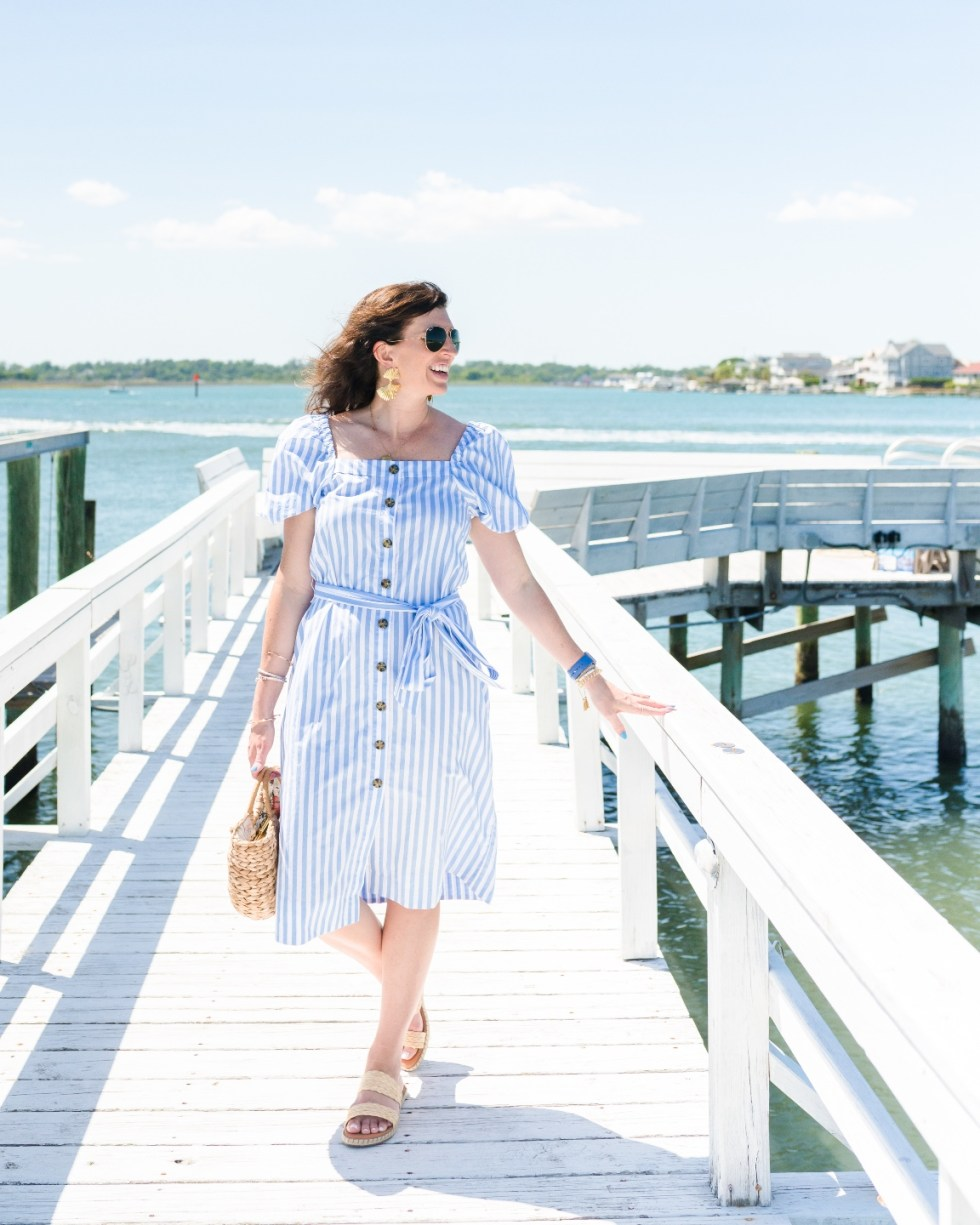 Style Diary: What I've Been Wearing this Spring - I'm Fixin' To - @imfixintoblog | Spring Essentials by popular NC fashion blog, I'm Fixin' To: image of a woman standing on a white wooden dock and wearing a white stripe button front puff sleeve dress.