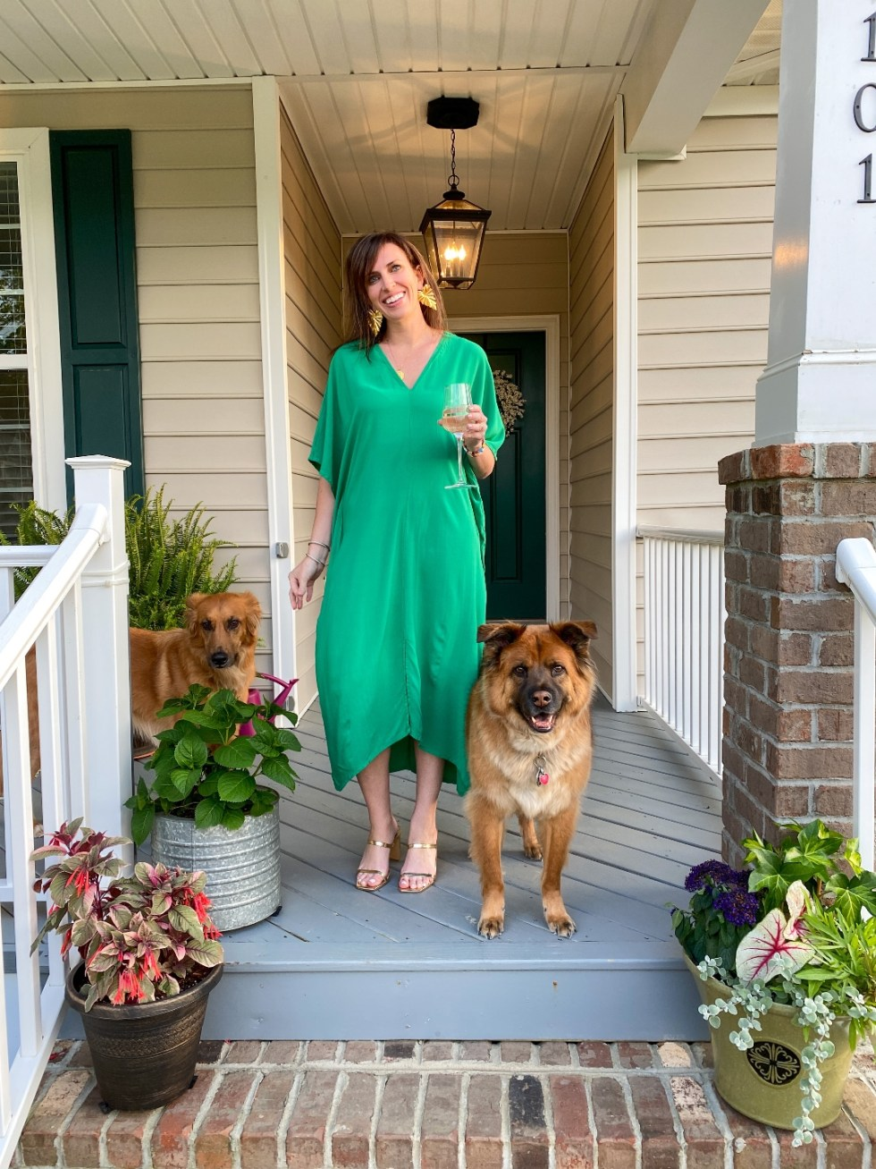 Style Diary: What I've Been Wearing this Spring - I'm Fixin' To - @imfixintoblog | Spring Essentials by popular NC fashion blog, I'm Fixin' To: image of a woman standing on her front porch with her two dogs and holding a glass of white wine while wearing. green dress, gold strap sandals, and gold statement earrings.