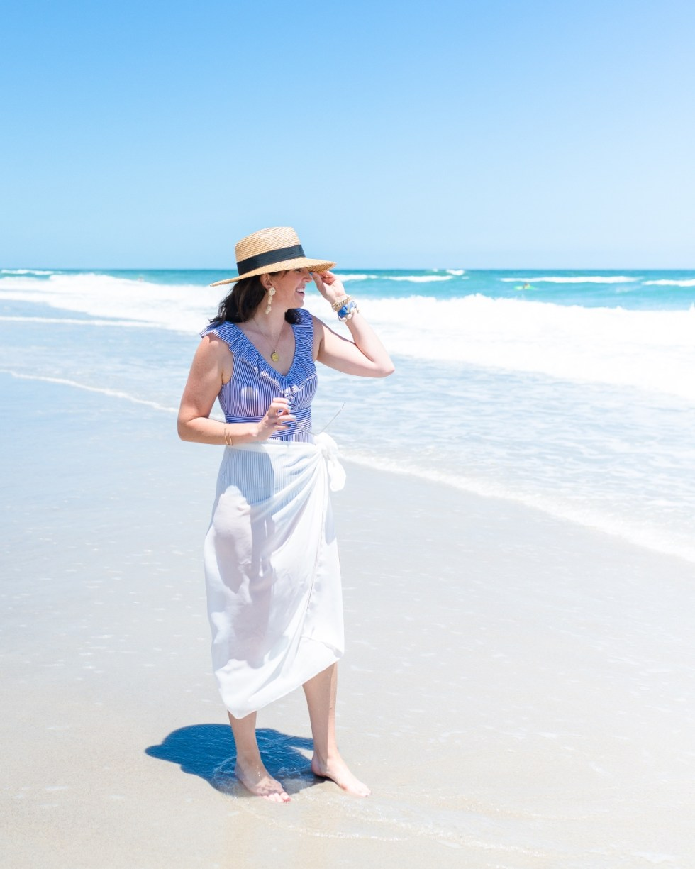 Style Diary: What I've Been Wearing this Spring - I'm Fixin' To - @imfixintoblog | Spring Essentials by popular NC fashion blog, I'm Fixin' To: image of a woman standing on a beach and wearing a blue and white stripe ruffle neck one piece swimsuit, white swimsuit cover up, and straw fedora hat.