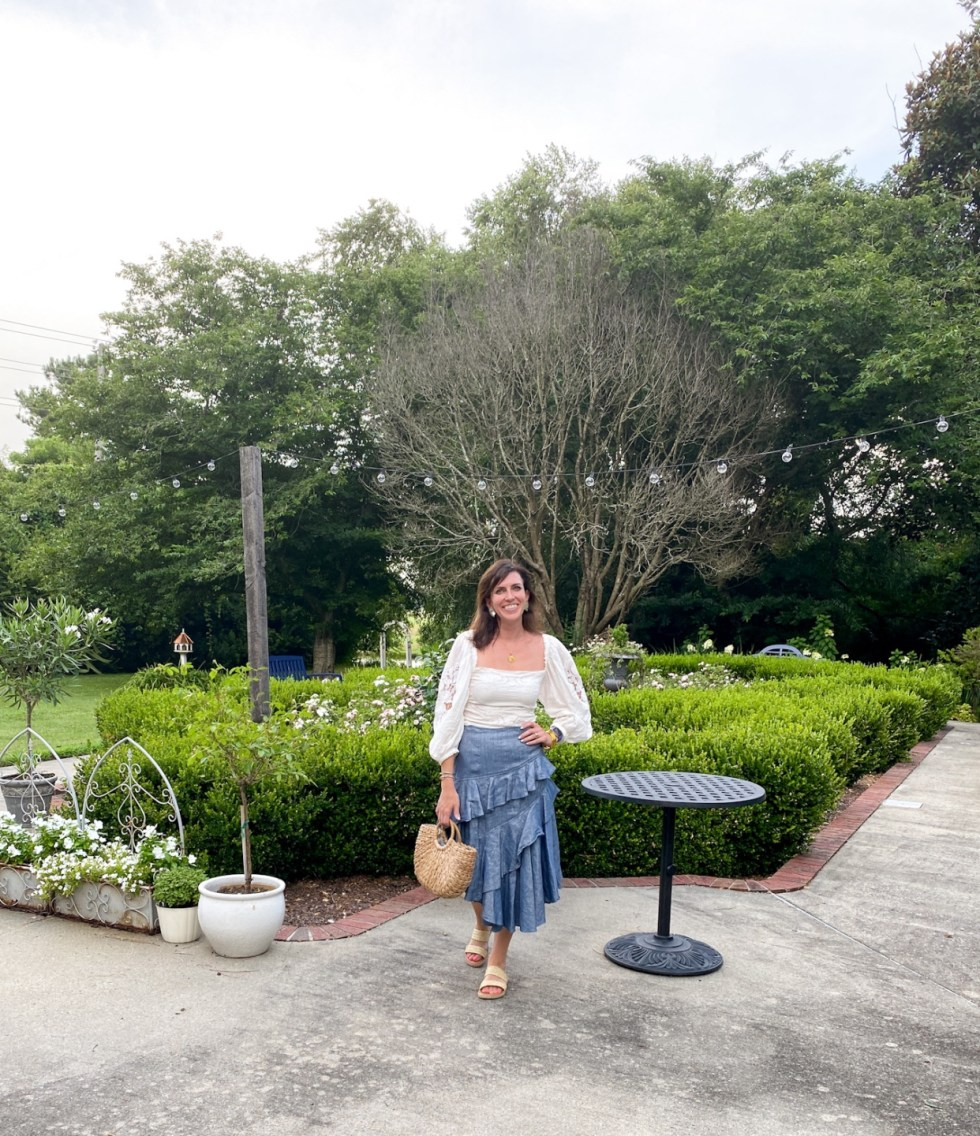 Top 10 Best Things to Do in Edenton, NC: A Complete Travel Guide - I'm Fixin' To - @imfixintoblog | Edenton Travel Guide by popular NC travel guid, I'm Fixin' To: image of a woman wearing a white eyelet puff sleeve top and chambray ruffle skirt while standing next to a hedge maze.