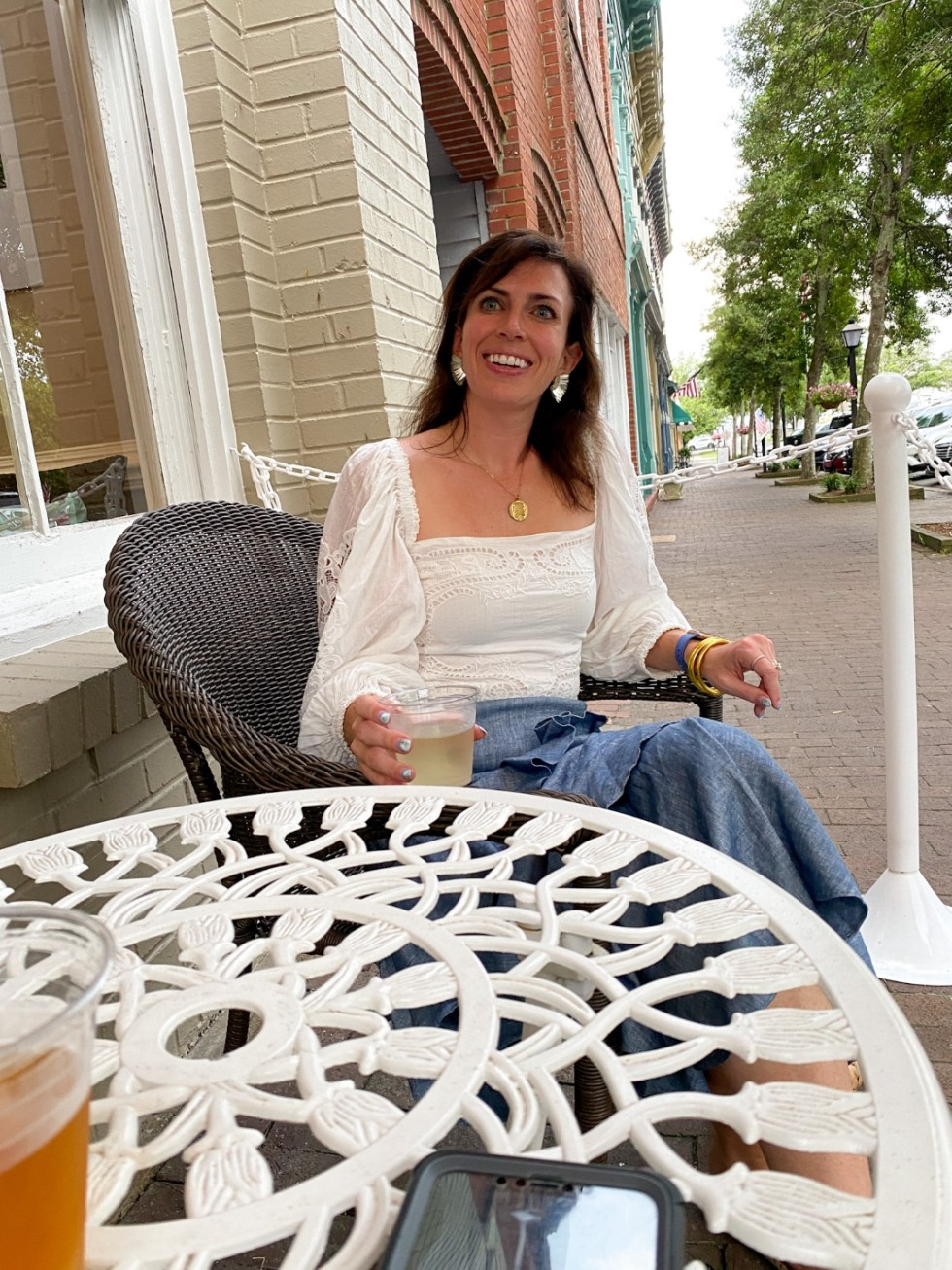 Edenton Travel Guide by popular NC travel guid, I'm Fixin' To: image of a woman sitting in a wicker chair and holding a drink in her hand.