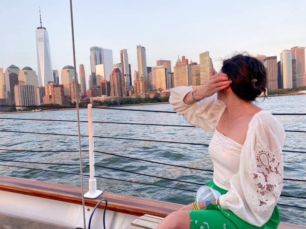 NYC Summer Weekend: Things to Do in NYC in the Summer - I'm Fixin' To - @imfixintoblog   NYC Summer Weekend by popular NC travel blog, I'm Fixin' To: image of a woman sitting on a boat and looking out at the NYC skyline.