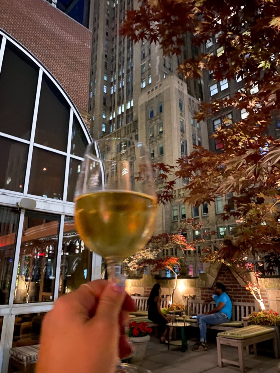 NYC Summer Weekend: Things to Do in NYC in the Summer - I'm Fixin' To - @imfixintoblog   NYC Summer Weekend by popular NC travel blog, I'm Fixin' To: image of a woman holding a glass of white wine.
