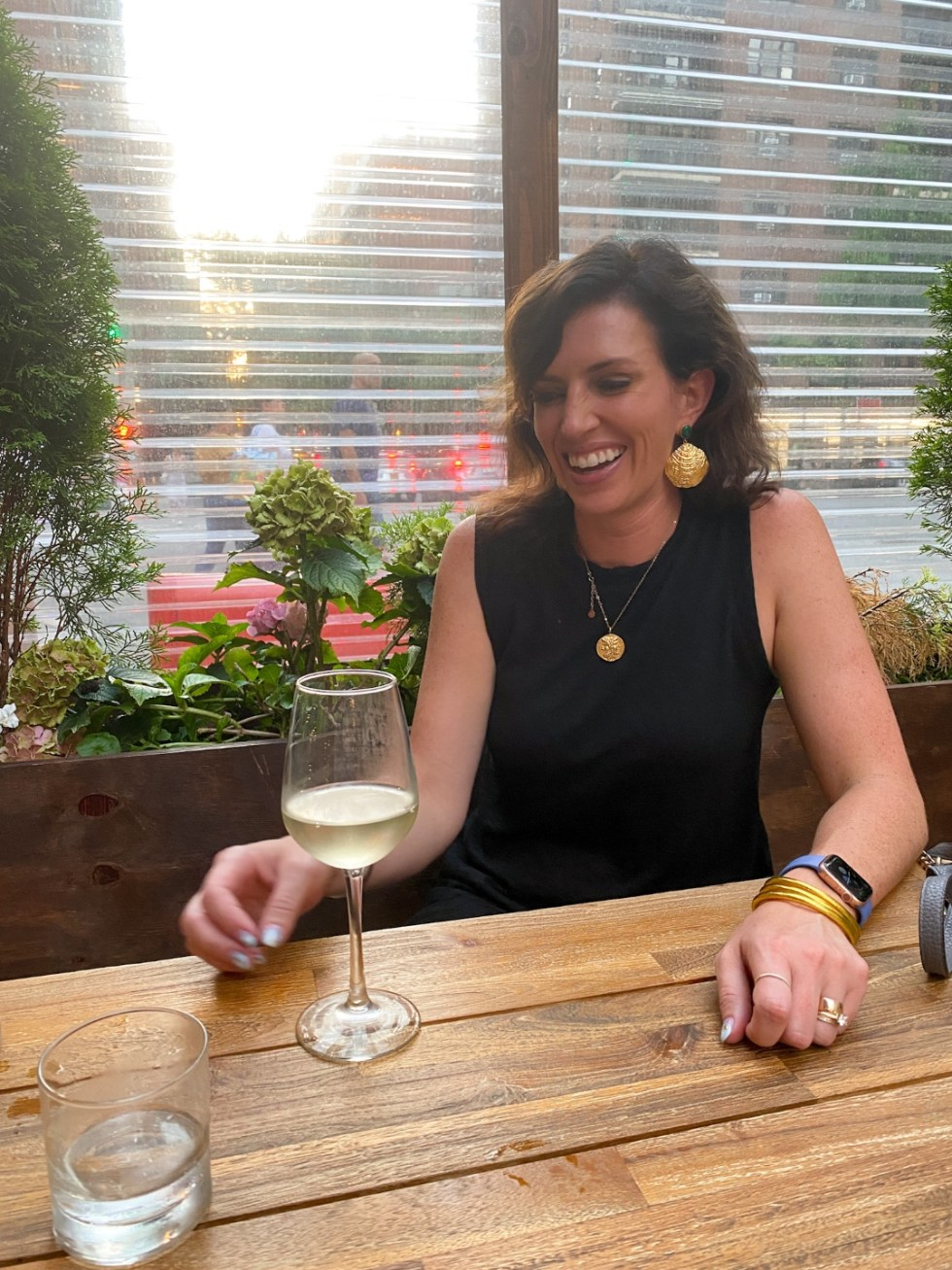 NYC Summer Weekend: Things to Do in NYC in the Summer - I'm Fixin' To - @imfixintoblog   NYC Summer Weekend by popular NC travel blog, I'm Fixin' To: image of a woman drinking a glass of white wine at Ted's Corner Tavern.