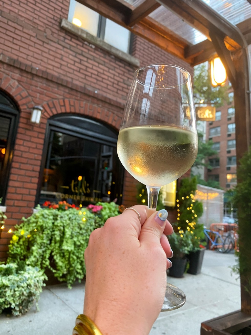NYC Summer Weekend: Things to Do in NYC in the Summer - I'm Fixin' To - @imfixintoblog   NYC Summer Weekend by popular NC travel blog, I'm Fixin' To: image of a woman holding a glass of white wine at Ted's corner tavern.