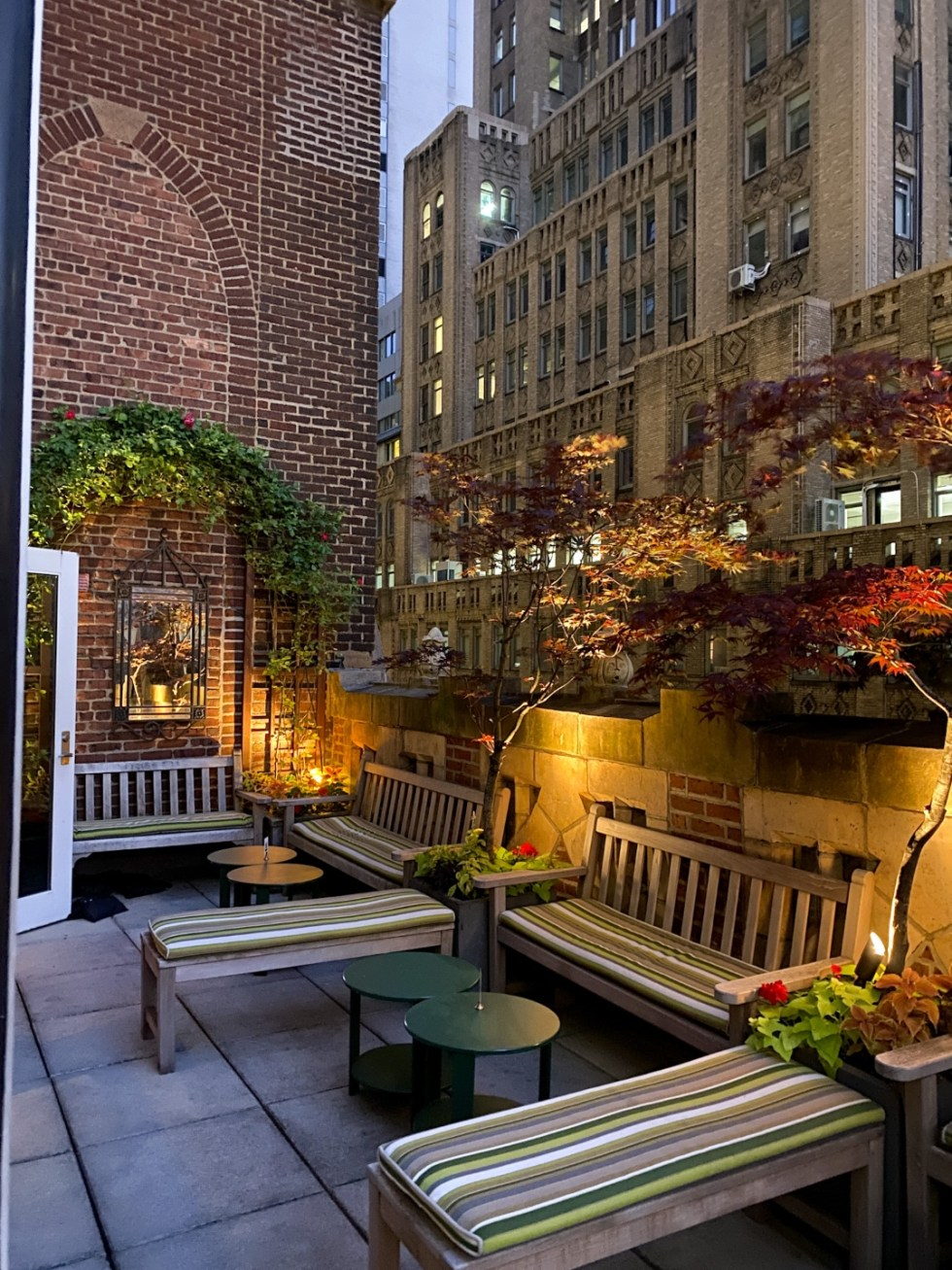 NYC Summer Weekend: Things to Do in NYC in the Summer - I'm Fixin' To - @imfixintoblog   NYC Summer Weekend by popular NC travel blog, I'm Fixin' To: image of a patio with wooden benches and black round coffee tables.