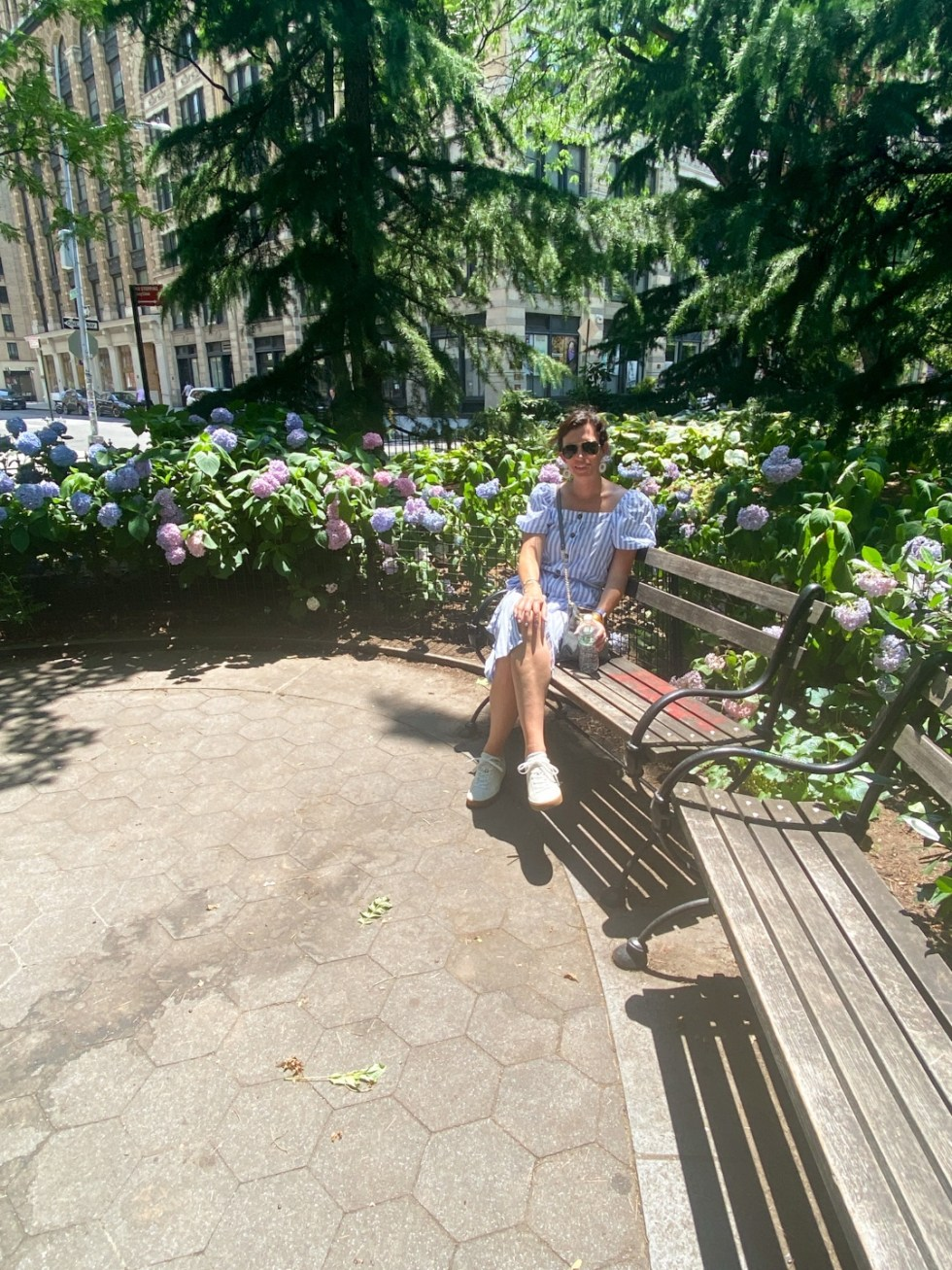 NYC Summer Weekend: Things to Do in NYC in the Summer - I'm Fixin' To - @imfixintoblog   NYC Summer Weekend by popular NC travel blog, I'm Fixin' To: image of a woman sitting on a wooden bench next to some purple hydrangea plants.
