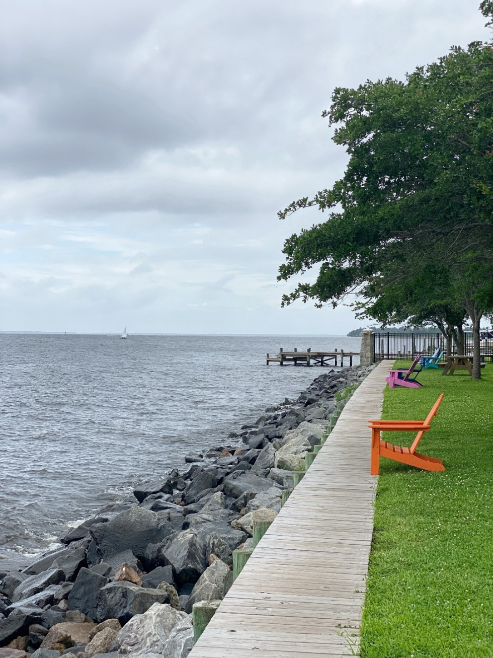 What to Do in Oriental, NC - I'm Fixin' To - @imfixintoblog | Things to do in Oriental NC by popular NC travel blog, I'm Fixin' To: image of colorful wooden lounge chairs on a ocean waterfront.
