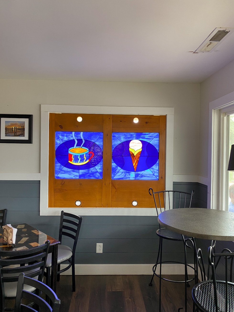 What to Do in Oriental, NC - I'm Fixin' To - @imfixintoblog | Things to do in Oriental NC by popular NC travel blog, I'm Fixin' To: image of a blue stain glass window with a image of a coffee cup and a ice cream cone.