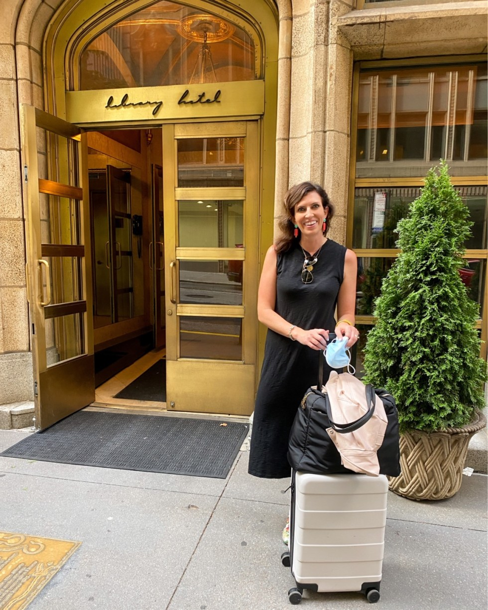 What to Pack for NYC by popular NC fashion blog, I'm Fixin' To: image of a woman standing outside the NYC Library Hotel with a cream rolling suitcase and wearing a black sleeveless dress and colorful statement earrings.