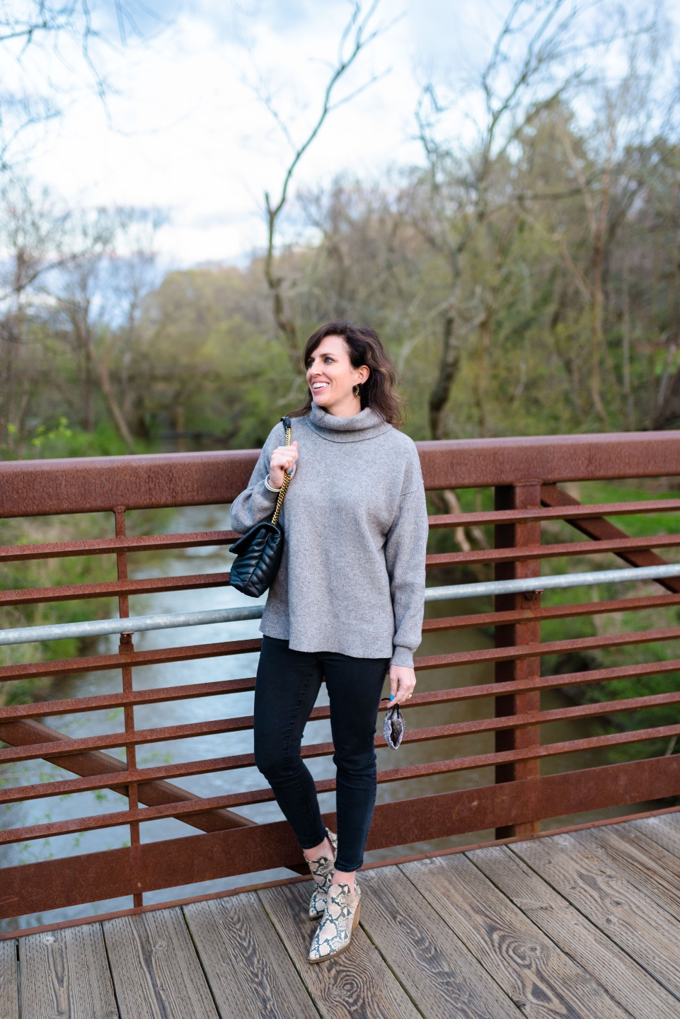 An Update on My North Carolina 100 County Tour - I'm Fixin' To - @imfixintoblog | Things to do in North Carolina by popular NC travel blog, I'm Fixin' To: image of a woman wearing a grey turtle neck sweater, black leggings, and snake print ankle boots while standing on a bridge.