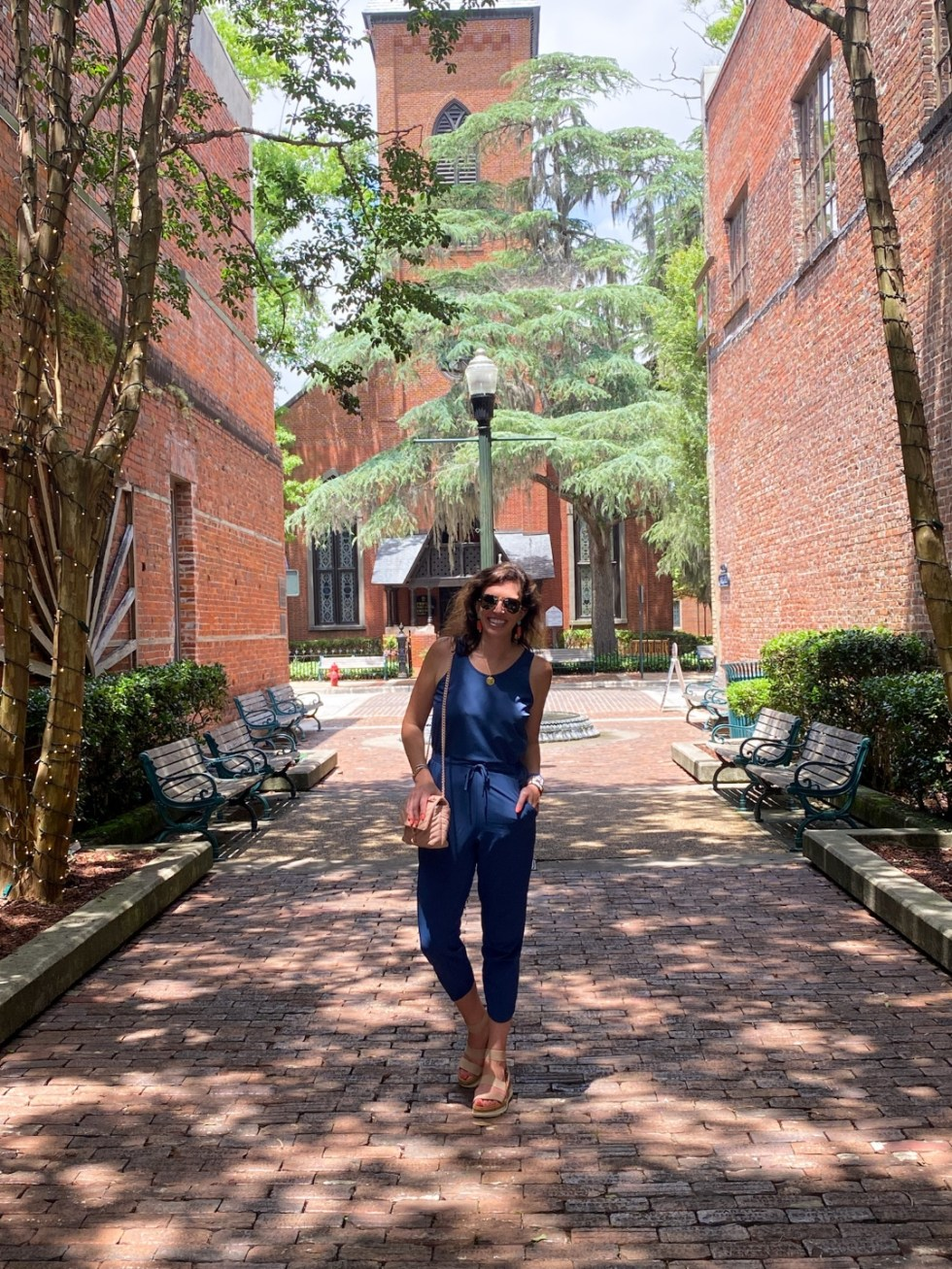 An Update on My North Carolina 100 County Tour - I'm Fixin' To - @imfixintoblog | Things to do in North Carolina by popular NC travel blog, I'm Fixin' To: image of a woman wearing a blue jumpsuit and standing on a brick paved road.