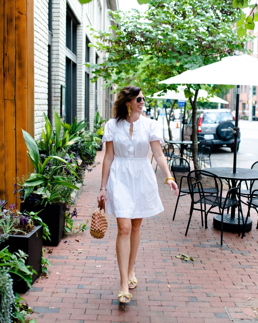 Labor Day Sales by popular NC life and style blog, I'm Fixin' To: image of a woman wearing. white dress, gold statement earrings, aviator sunglasses, bow accent shoes and holding a woven straw bag while walking down a paved brick sidewalk.