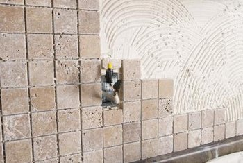 Mortar vs  Tile Adhesive When Installing a Backsplash   Home Guides     Both types of adhesive are applied to the backsplash in the same way