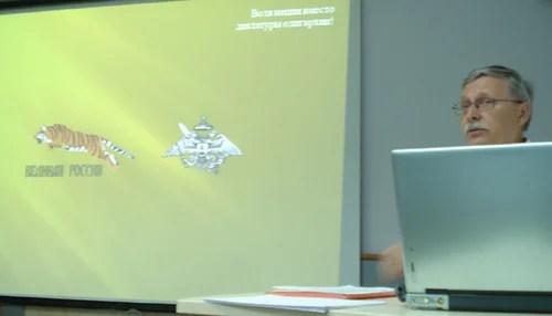 Sergey Pykhtin mit den Symbolen der Partei Großrussland (Ein springender Tiger) und des Russischen Reichsbund Ordens (Adler mit Schwert) am Bildschirm