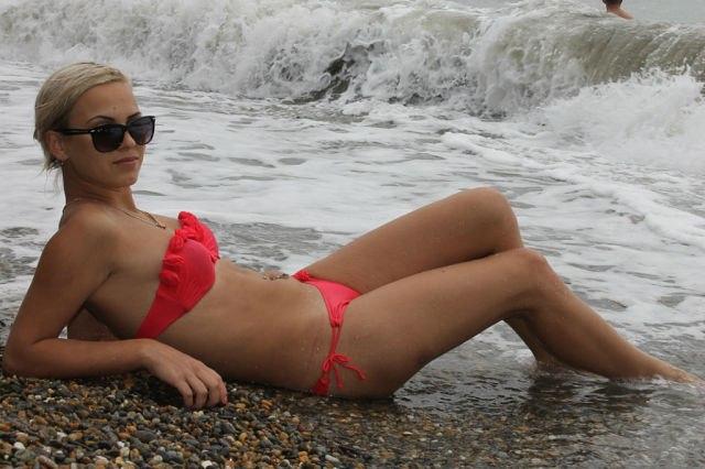 Блондинка в солнцезащитных очках и красном купальнике