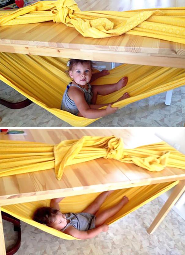 При помощи простыни и стола можно сделать для детей отличный гамак.