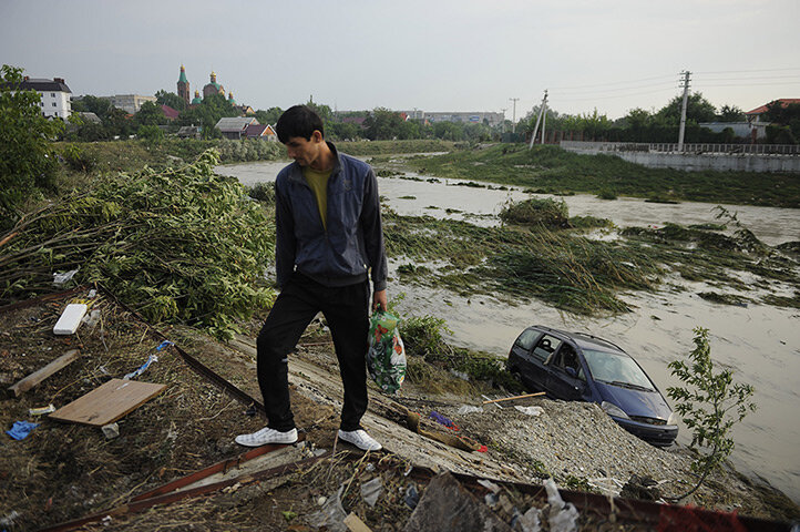 A man walks past a submerged car on a flooded street in Krymsk