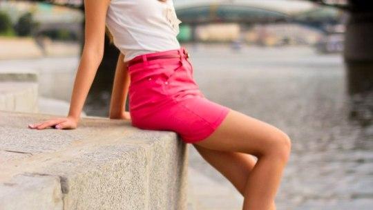 Длинноволосая милашка  в розовой юбке на ступеньках