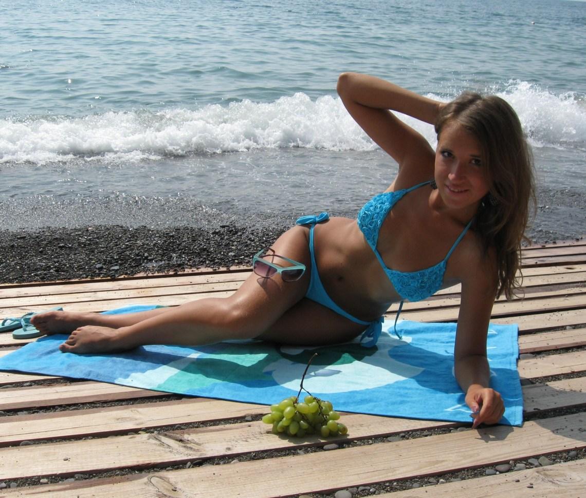 Стройная девчонка загорает на пляже