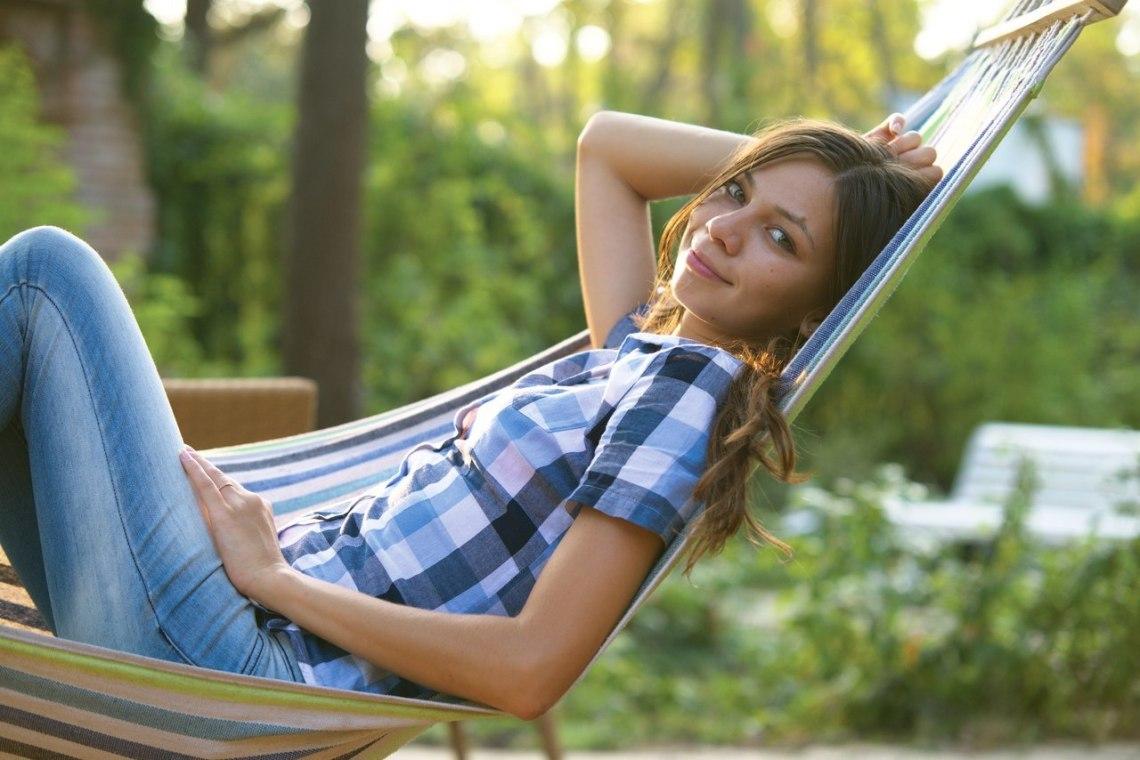 Веселая девочка в синей клетчатой рубашке в деревне