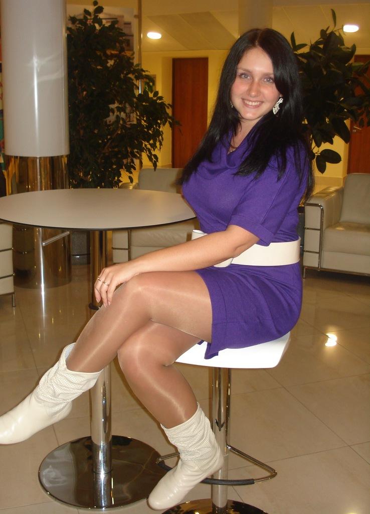 Красотка брюнетка в сиреневом платье с белым  поясом