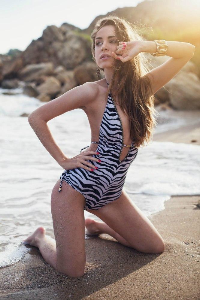 Девушка в закрытом  купальнике на коленях