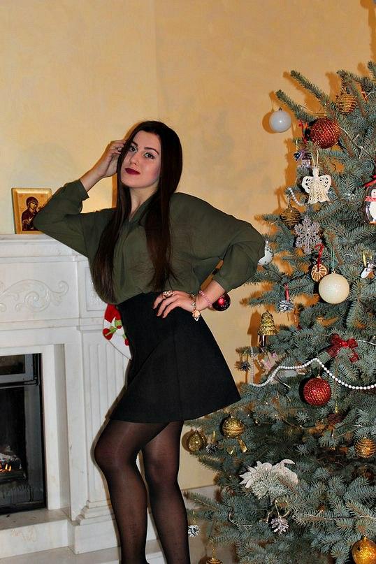 Девчонка в зеленой кофточке возле новогодней елки