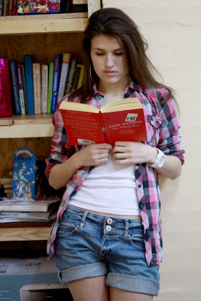 Красотка в клетчатой рубашке читает книгу