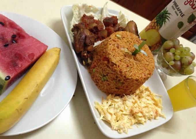 Jollof rice with salad, pepper kpomo and fried chicken