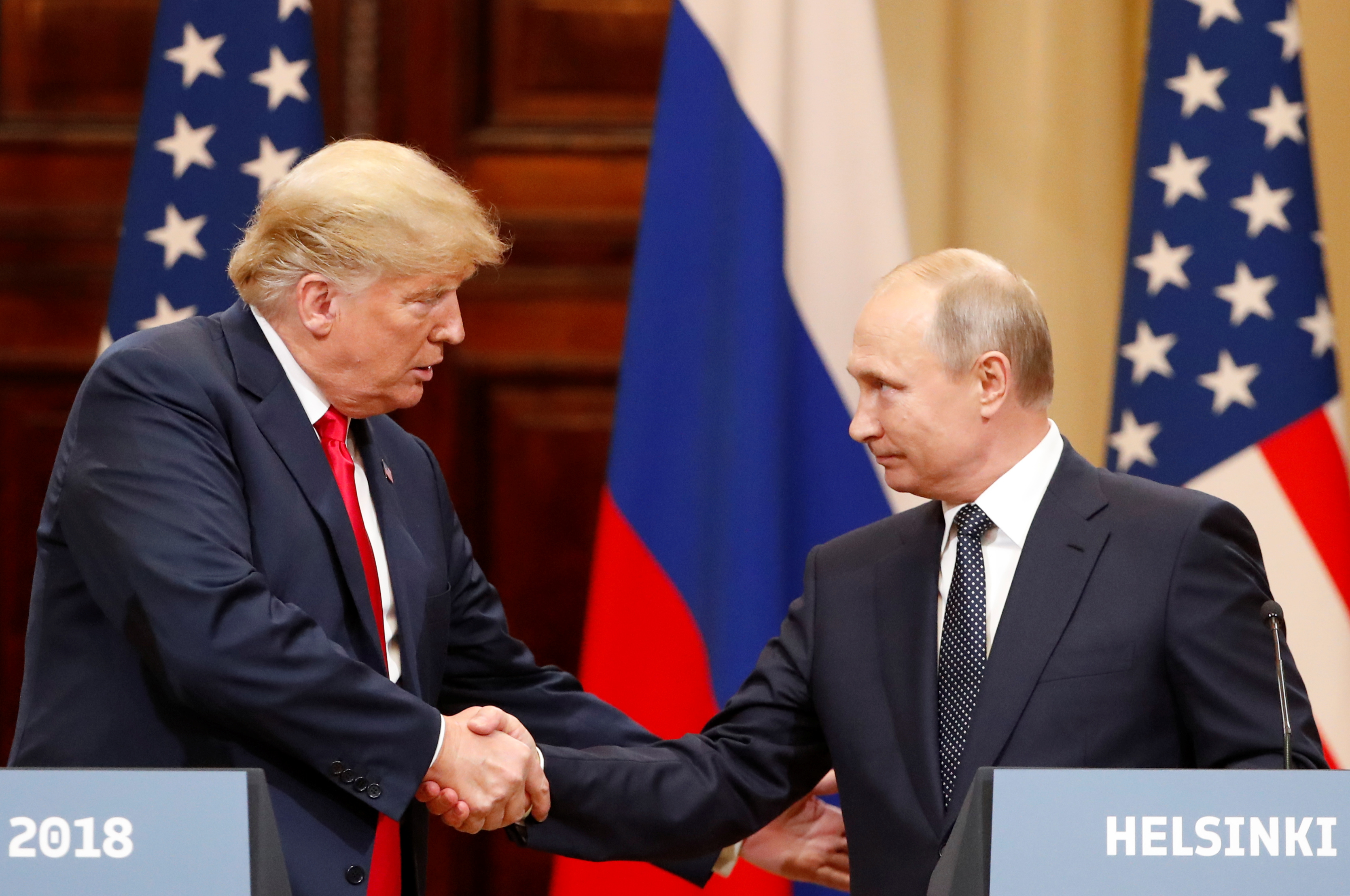 Slide 1 of 17: U.S. President Donald Trump and Russian President Vladimir Putin shake hands as they hold a joint news conference after their meeting in Helsinki, Finland July 16, 2018. REUTERS/Grigory Dukor