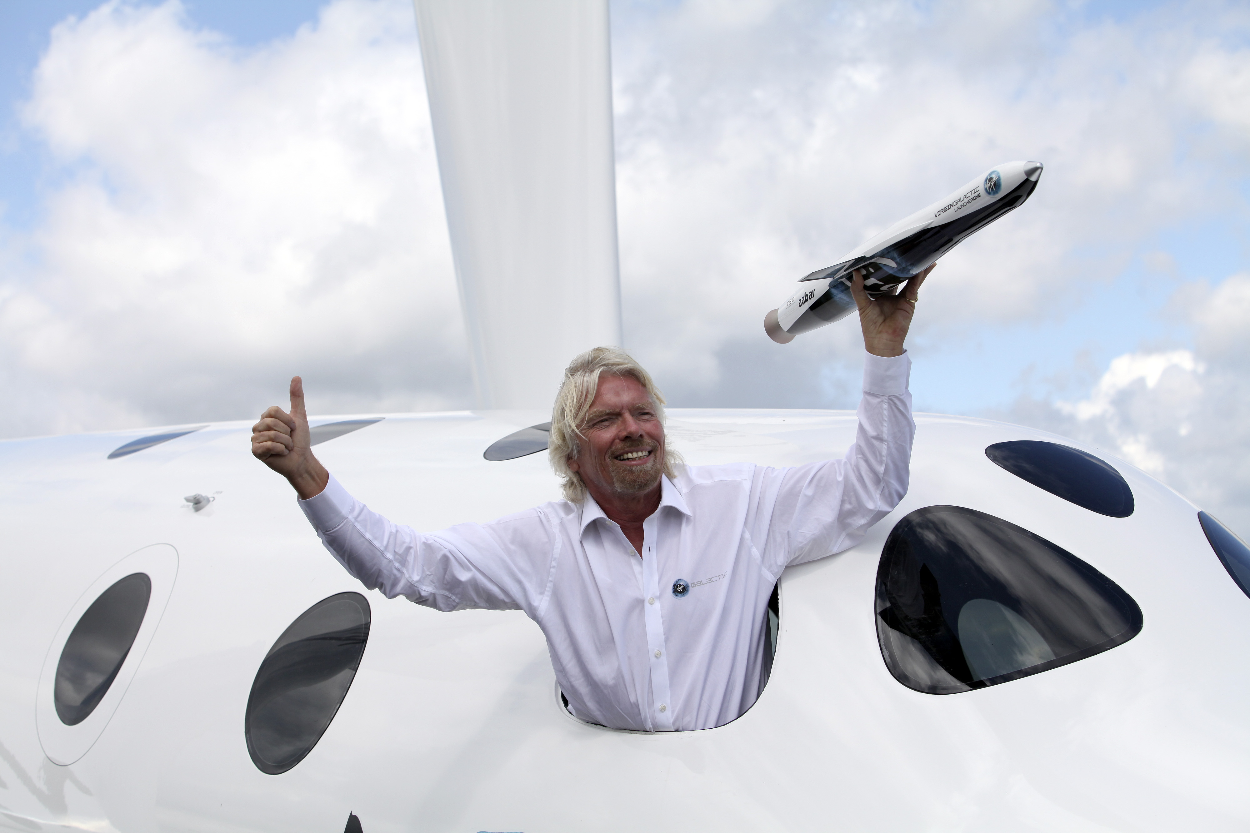 Richard Branson poses for photographers with a model of the LauncherOne rocket from the window of Virgin Galactic's SpaceShipTwo, on the third day of the Farnborough International Air Show in Farnborough, U.K., on Wednesday, July 11, 2012.