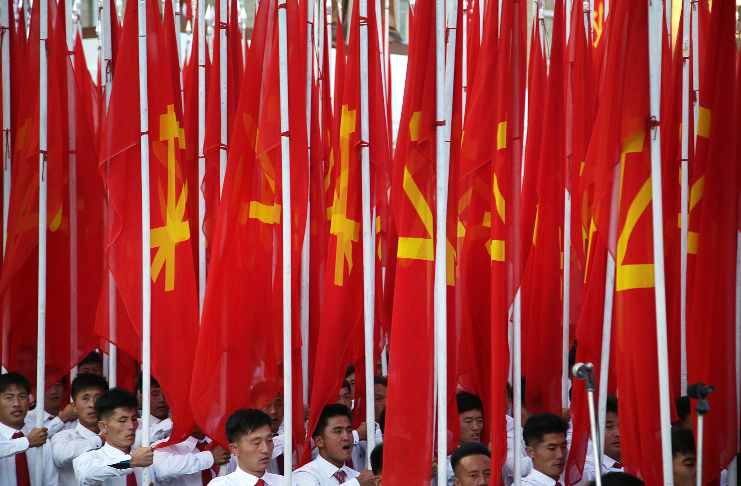 North Korean men carrying the ruling Workers' Party flag, march during a military parade in Pyongyang, North Korea, Saturday, Oct. 10, 2015. North Korean leader Kim Jong Un declared Saturday that his country was ready to stand up to any threat posed by the United States as he spoke at a lavish military parade to mark the 70th anniversary of the North's ruling party and trumpet his third-generation leadership. (AP Photo/Wong Maye-E)