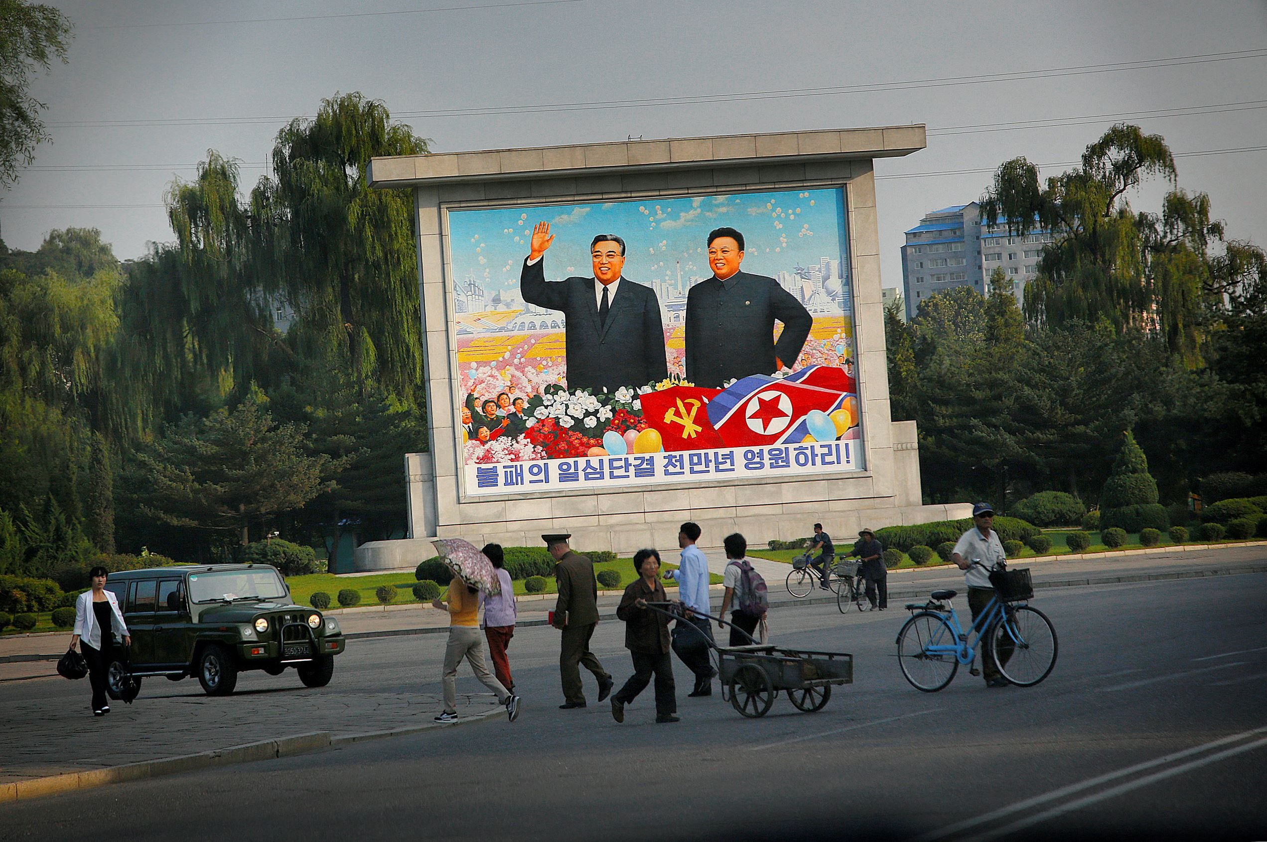 In this Tuesday, Sept. 15, 2015, photo, North Koreans walk by a mural of late North Korean leaders Kim Il Sung, left, and Kim Jong Il, in Pyongyang, North Korea. North Korea is in high gear as it prepares to mark the 70th anniversary of the founding of its ruling party. (AP Photo/Wong Maye-E)