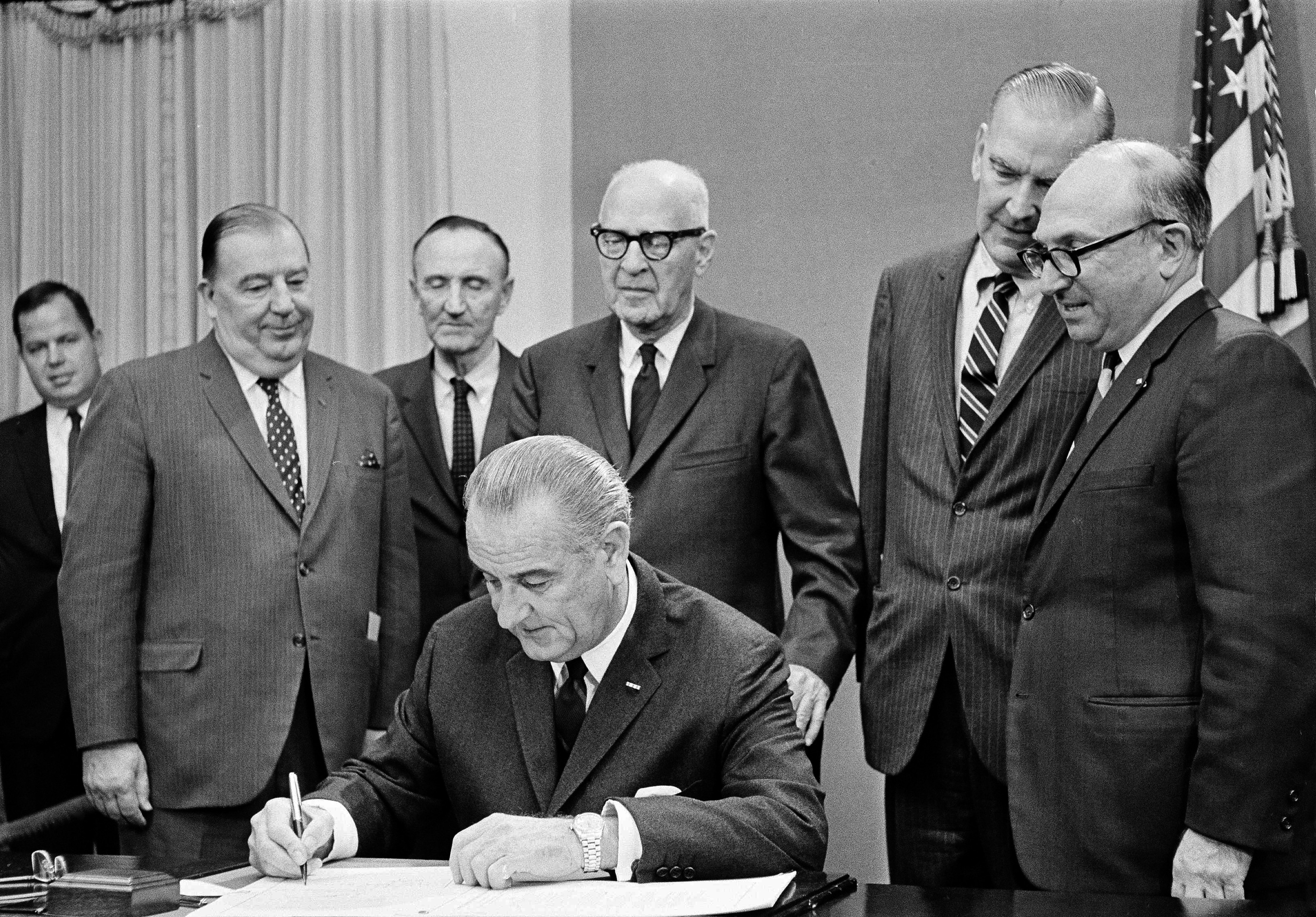 "President Lyndon B. Johnson signs a bill which authorizes a $576 million health service program Oct. 15, 1968. During the signing ceremonies, the president said the program ""will greatly strengthen the right of every citizen to have good health."" Standing are, from left: Senators Jennings Randolph (D-W.V.); Mike Mansfield (D-Mont.); and Lister Hill (D-Ala.)."