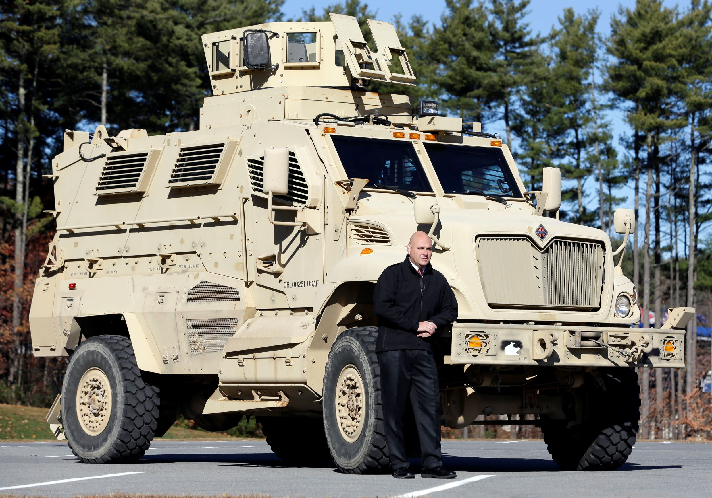 In this Wednesday, Nov. 13, 2013 photo, Warren County Undersheriff Shawn Lamouree poses in front the department's mine resistant ambush protected vehicle, or MRAP, in Queensbury, N.Y.