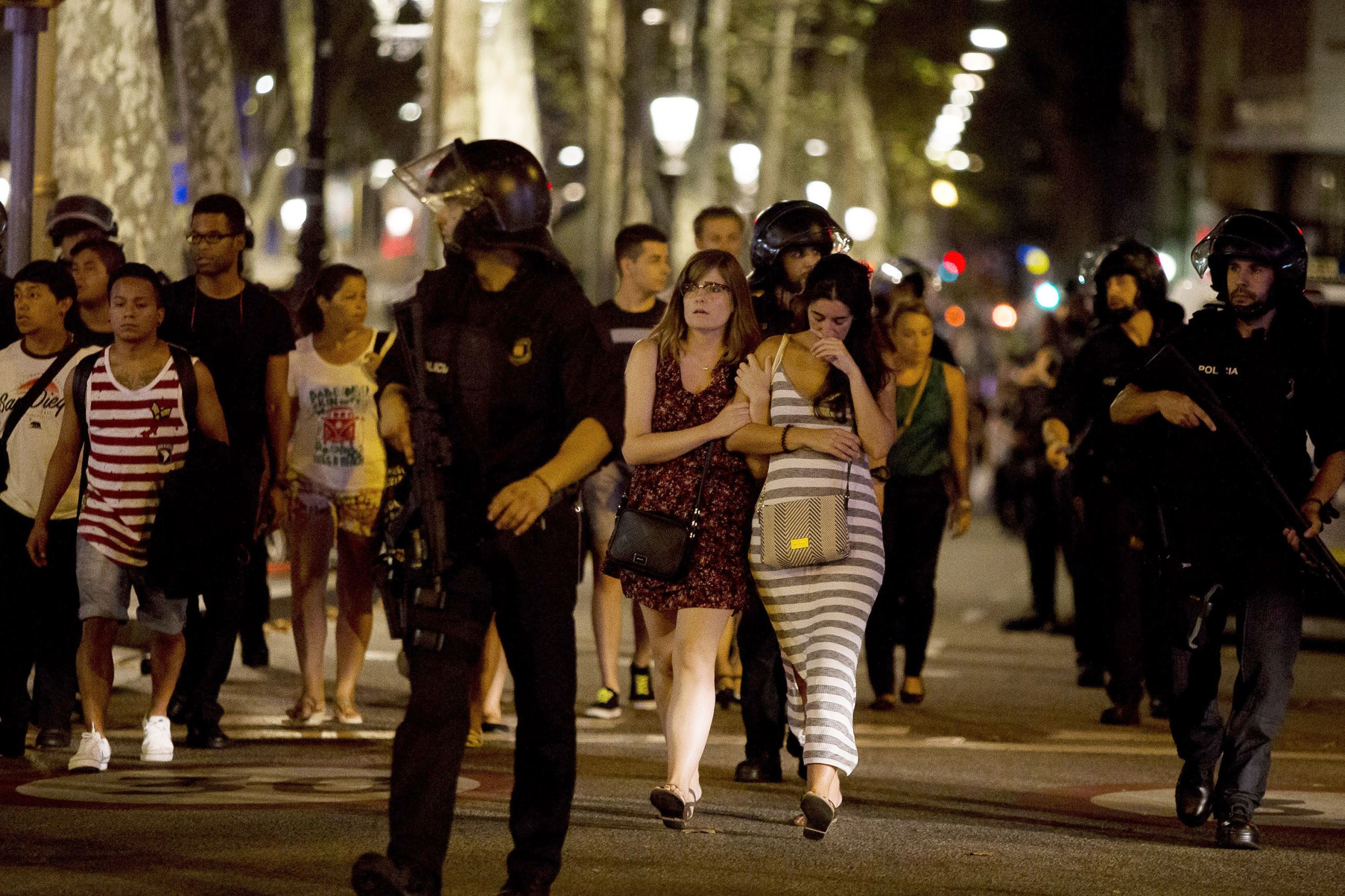 Slide 2 of 25: BARCELONA, SPAIN - AUGUST 17: Police officers evacuate people from a shop at Las Ramblas as they take security measures at the area after a van plowed into the crowd, injuring several people in Barcelona, Spain on August 17, 2017. (Photo by Albert Llop/Anadolu Agency/Getty Images)