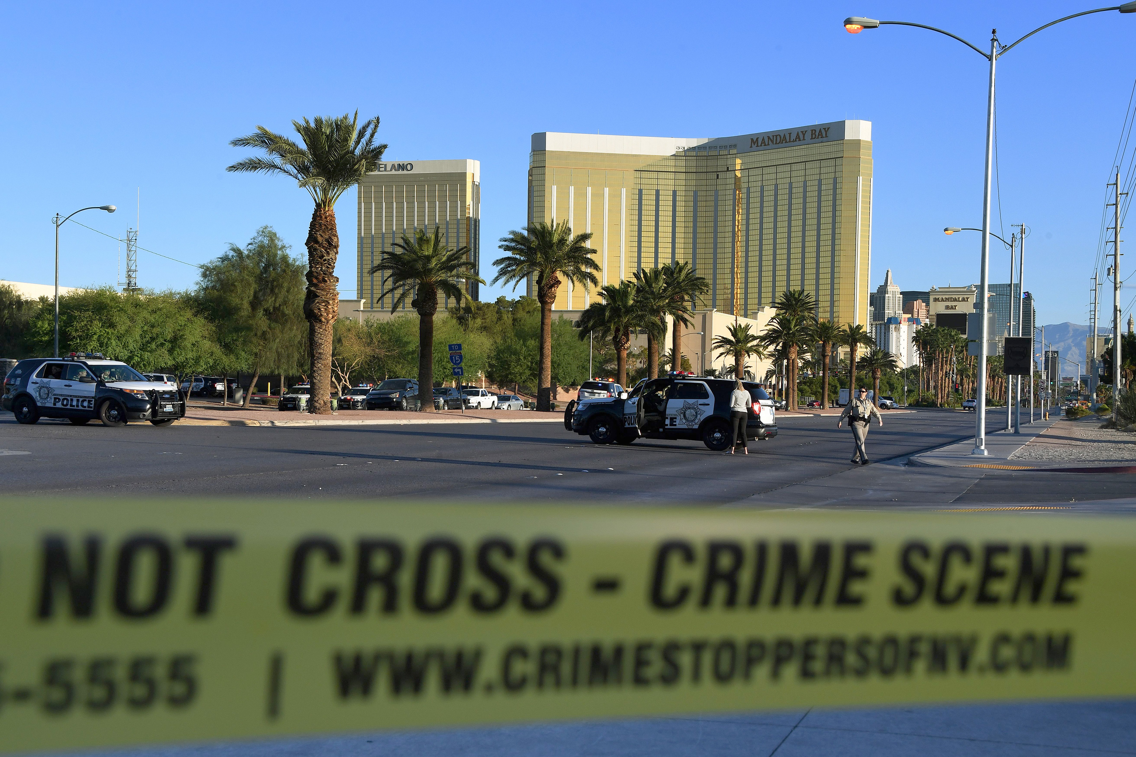 Slide 1 of 26: Crime scene tape surrounds the Mandalay Hotel (background) after a gunman killed at least 50 people and wounded more than 200 others when he opened fire on a country music concert in Las Vegas, Nevada on October 2, 2017.  Police said the gunman, a 64-year-old local resident named as Stephen Paddock, had been killed after a SWAT team responded to reports of multiple gunfire from the 32nd floor of the Mandalay Bay, a hotel-casino next to the concert venue.