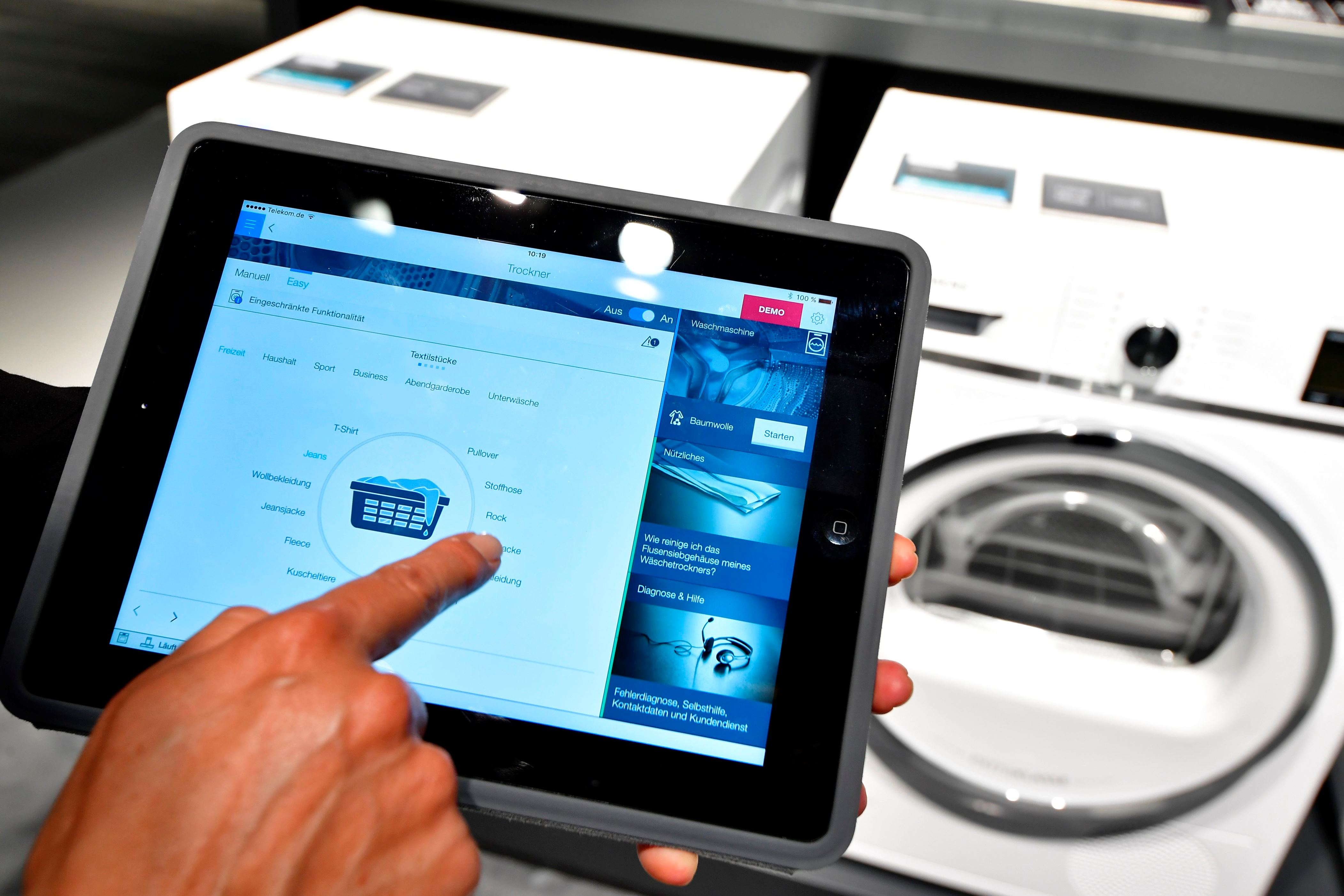"A fair worker uses a tablet to operate a tumble dryer during a demonstration how to operate smart controlled household appliances for ""IQ800"" washing and drying machines at the booth of Siemens as preparations are under way for the consumer electronics fair IFA in Berlin on August 30, 2017. household appliances in a smart home The fair is open for the public from September 1 to 6, 2017. / AFP PHOTO / TOBIAS SCHWARZ        (Photo credit should read TOBIAS SCHWARZ/AFP/Getty Images)"