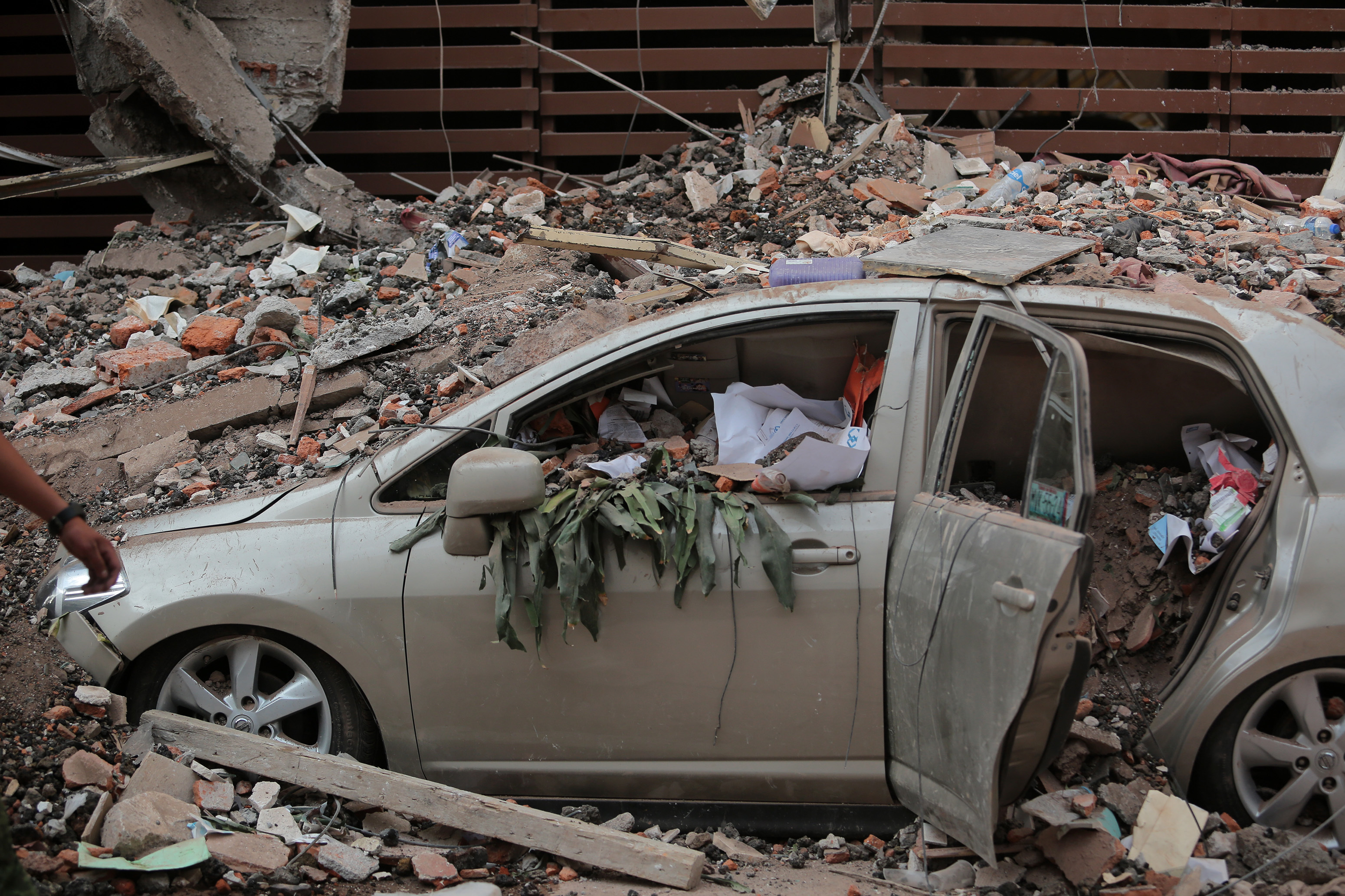 Slide 5 of 42: MEXICO CITY, MEXICO - SEPTEMBER 19: A car is seen destroyed because of the rubble from a building knocked down by a magnitude 7.1 earthquake that jolted central Mexico damaging buildings, knocking out power and causing alarm throughout the capital on September 19, 2017 in Mexico City, Mexico. The earthquake comes 32 years after a magnitude-8.0 earthquake hit on September 19, 1985. (Photo by Hector Vivas/Getty Images)